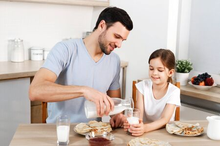 Happy father and daughter have breakfast at kitchen, eats delicious pancakes with jam, drink milk, enjoys delicious food prepared by mother. Family apetizes yummy sweet dish. Eating and people concept.