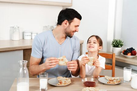 Affectionate pleasant looking father and his little daughter eat tasty morning meal at kitchen, communicate with each other.