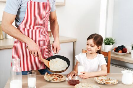 Cropped shot of man in apron involved in cooking, fries delicious pancakes for his daughter, preapres breakfast, brings up child. Cheerful kid drinks milk with flannel cake. Family breakfast.