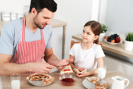 Photo of friendly family have breakfast together. Bearded man spreads jam on thin fried pancake, sits with her little daughter at kitchen, going to have sweet delicious dessert. Parenthood concept.