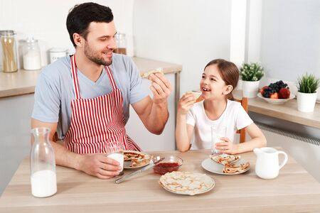 Cheerful handsome young male and little child eat pancakes together, drinks fresh milk, enjoy breakfast at kitchen, being in good mood, going to have walk in park. Family and childhood concept.