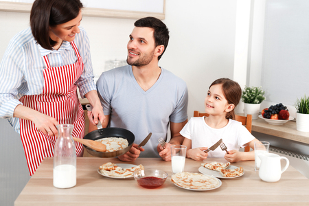 Photo of hard working wife, husband and their daughter sit together at kitchen table, going to eat delicious pancakes, enjoy togetherness.