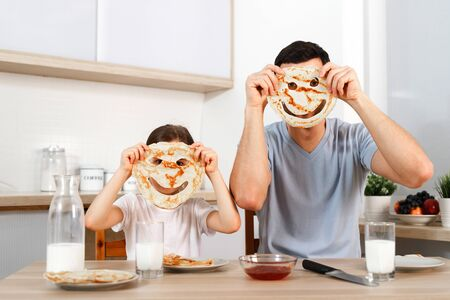 Funny pretty daughter and father make faces with pancakes, make fun together at kitchen during weekends, enjoy delicious flannel cake, foolish.