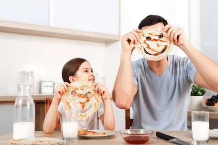Glad positive young father foolishes with her small daughter at kitchen, make faces from pancakes, have tasty breakfast, pose at camera, drink fresh milk, eat flannel cakes with sweet jam. Stock Photo
