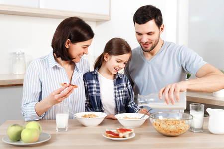 Happy young parents and their lovely daughter sit together at kitchen table, eat flakes, have healthy breakfast, enjoy good morning, have friendly relationship. Family and eatting concept.