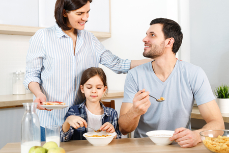 Three family members have delicious healthy breakfast at kitchen, eat cornflakes with milk, enjoy togetherness and domestic atmosphere.