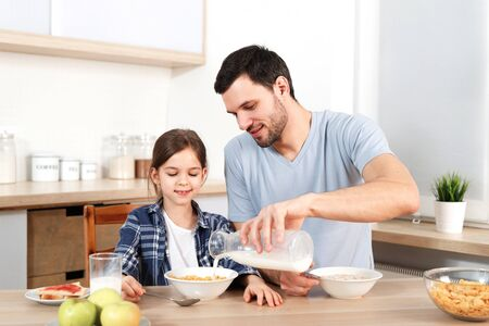 Young handsome father pours milk in bowl with flakes, prepares breakfast for small child, sit together at kitchen, have healthy food, enjoy togetherness. Friendly family being at home, eat.