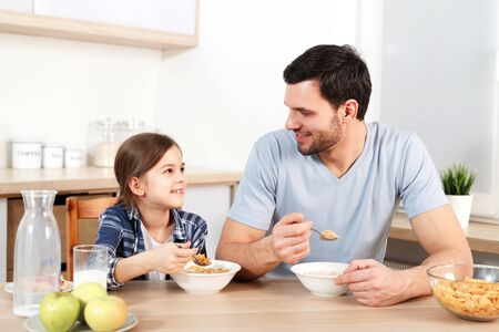 Adorable little kid and her father eat flakes together, have pleasant conversation with each other, sit at kitchen table, eat only healthy food. Parenthood, childhood and eatting concept.