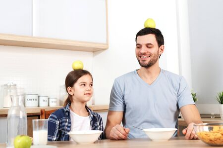 Funny young dad and daughter sit next to each other, eat delicious cornflakes, keep apples on head, demonstrate that they eat only healthy food, have good relationships and understanding.