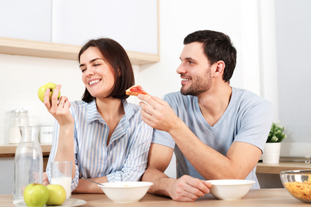 Happy couple spend free time or weekend together at kitchen, glad husband suggests wife to eat snack, she refuses as eats green apple, have breakfast. Family, cooking and relations concept.