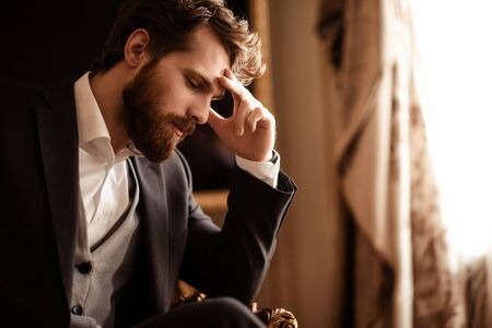 Close up shot of pensive bearded man in elegant formal suit, ponders about something, has some problems with finances, involved in business, has sad expression. Unhappy businessman poses indoor. Stock Photo