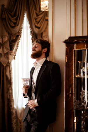 Vertical shot of pleased bearded young businessman wears black formal suit holds glass and drinks beverage, stands in room decorated with luxurious curtains and furniture, feels relaxation.