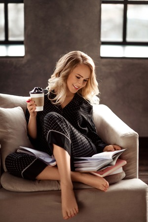 Beautiful cheerful young blonde female in pyjamas enjoys morning coffee, reads book as prepares for presentation, sits o comfortable armchair in living room. People, rest and leisure concept.