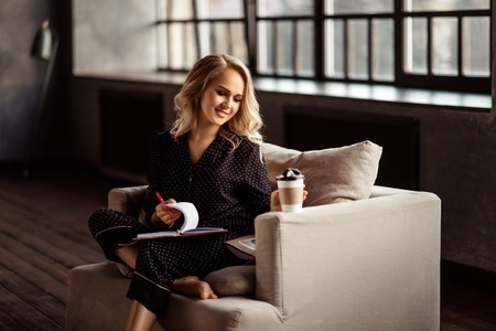 Beautiful young female student prepares for upcoming exam early in morning, writes notes in notepad, enjoys hot coffee from paper cup, sits on comfortable armchair, cozy domestic atmosphere Stock Photo