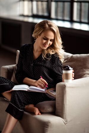 Concentrated talented female writer dressed casually, writes down some ideas for new article, drinks coffee from takeaway cup, sits in comfortable armchair, enjoys calm domestic atmosphere at home. Stock Photo