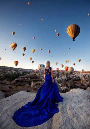 Back view of blonde female dressed in elegant long blue dress, stands back on high hill, admires many parachutes in sky and sunrise, enjoys calm atmosphere and loneliness. Freedom and quietness.