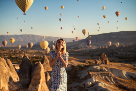 Horizontal outdoor shot of happy blonde young smiling woman in dress being excited as stands on high mountain looks upwards and sees many parachutes flying in air, admires beautiful view on hill. Stock Photo