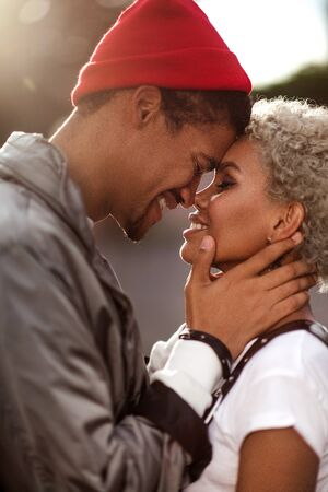 Vertical close up portrait of happy peased people in love being of different nation, express their good relationship and feelings. Dark skinned male in trendy hat looks sincerely in girlfriend s eyes.