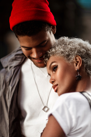 Close up shot of beautiful female mulatto with trendy hairdo and pensive look stands closely to her dark skinned male in red hat, demonstrate real love and good relationship. Ethnicity and people.