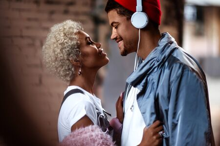 Happy Afro American man in headphones and his female friend with curly hairdo stand close to each other. Stock Photo