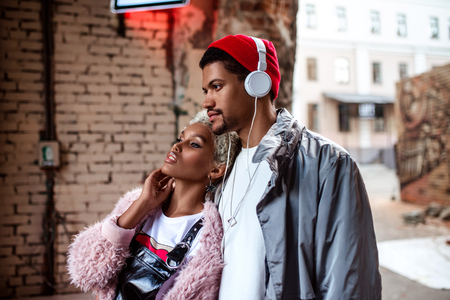 Attractive mulatto woman and her dark skinned stylish friend who listens music with headphones, walk together in street, looks at something with thoughtful expression. People and lifestyle concept. Stock Photo