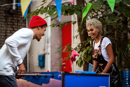 Two mixed race female and male friends play table football outdoor, entertain themselves. Positive stylish mulatto people play outdoor game together. People, recreation and entertainment concept.