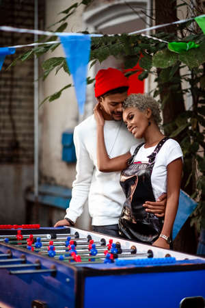 Vertical shot of pleasant looking mixed race female and her boyfriend embrace each other, stand near table football game, like playing. Dark skinned hipster man and mulatto woman pose outdoor.