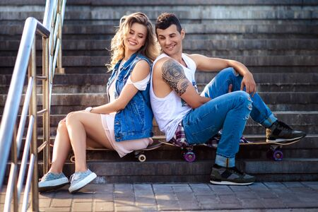 Cheerful girlfriend and boyfriend sit together backs on stairs, have rest after going skateboarding in open air, satisfied with summer weather, dressed in fashionable clothing. Active lifestyle.