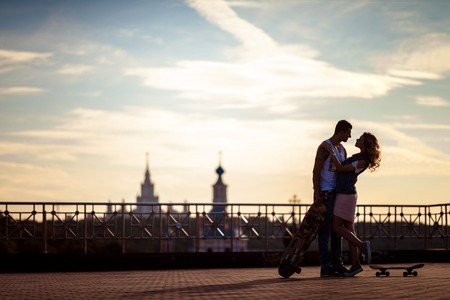 Outdoor shot of affectionate young couple pose against beautiful city view and sky, have rest after skateboading, demonstrate true love and perfect relationships. Talented skateboarders togehter.