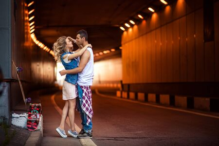 Portrait of female and male skaters embrace passionately, going to kiss, stand against tunnel background, recreat after active skateboarding in open air. People, relations and sporty lifestyle.