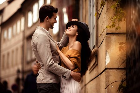 Passionate gorgeous young couple embrace each other while walk across ancient city. Cheerful elegant cute female model wears stylish hat, looks with cheerful expression in her boyfriend s eyes. Stock Photo