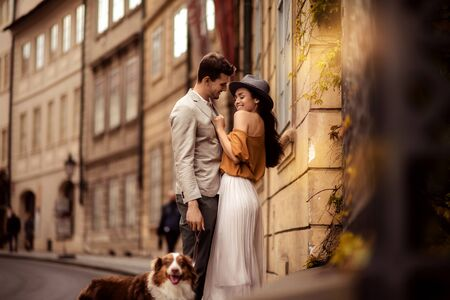 Happy stylish man strolls with dog, embraces his beautiful elegant girlfriend, have good relationship and feel true love, pose against ancient builduing background while walk on street together Stock Photo
