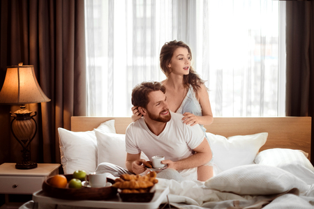 Satisfied family couple have breakfast in bed, enjoy delicious croissants, coffee and fruit, look positively away, sits against cozy domestic interior in bedroom. Bed time and relationship concept
