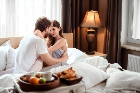 Passionate male and female embrace each other, look with love, spend their honeymoon in luxury hotel, enjoy delicious breakfast. Affectionate young couple in cozy bedroom enjoy togetherness Stock Photo