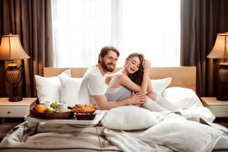 Smiling bearded man being happy to spend free time with his female lover, sit together in comfortable bed in hotel room, going to have breakfast. Luxury apartaments. Love and relationship concept.