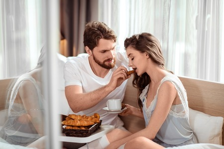 Love and care concept. Affectionate young handsome bearded male feeds his cute girlfriend with croissant, sit together at comfortable bed. Pretty woman with drink enjoys care from her boyfriend