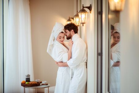 Bearded male and his wife wears white bathrobes and towel on head, hug each other, feel relaxed after taking bath in hotel, going to have sleep. Adorable woman and her husband pose after shower