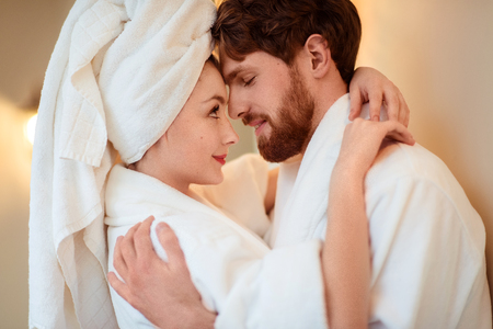 Close up shot of beautiful woman and her husband cuddle each other, express love, wear comfortable bathrobes, relax after taking shower or having spa procedure in luxury hotel. Beauty and relations
