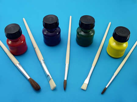 brushes and bottles of paint on a blue bakcground Stock Photo
