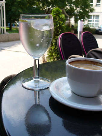 glass of cold mineral water and cup of coffee on a table in the bar Stock Photo