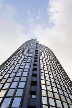 edificio per uffici di vetro con cielo e nuvole in background