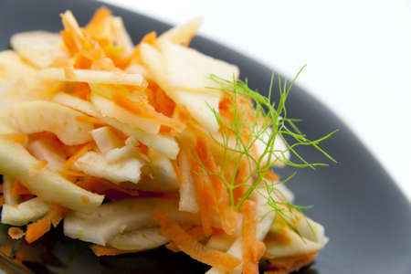 Fennel salad with carrots and apples on a black plate