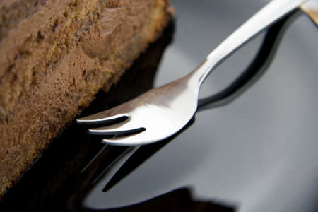 Slice of chocolate cake on a black plate with fork