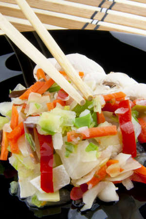 Chinese vegetables with chopsticks on a black plate