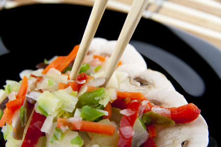 Grabbing chinese vegetables with chopsticks on a black plate