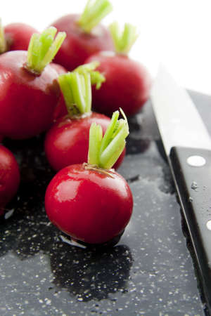 Red radishes with knife on a black chopping board