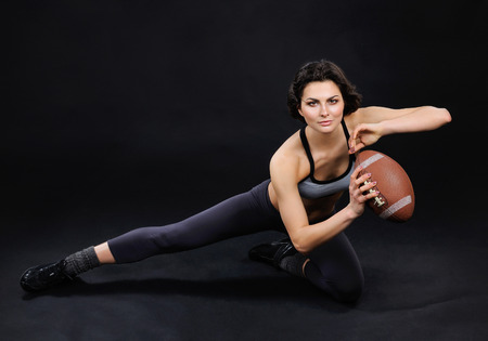 rugby football: Athletic brunette posing as American football woman players in studio