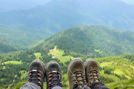 hiking boots: Hiking boots of traveler sitting on high mountain top in travel. Freedom concept Stock Photo