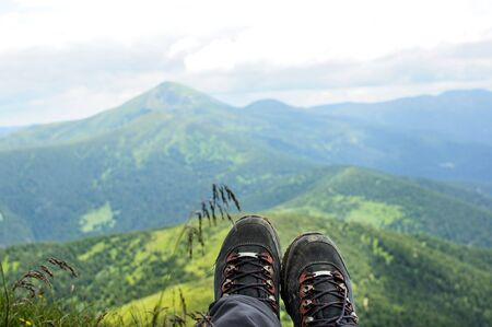 summer shoes: Hiking boots of traveler sitting on high mountain top in travel. Freedom concept Stock Photo