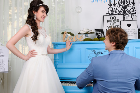 jewess: Close up of beautiful woman and man playing on piano. Wedding dress. Wedding accessories